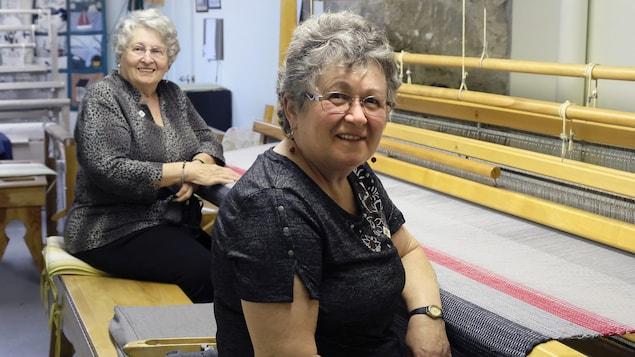 Deux femmes sourient devant une couverture.
