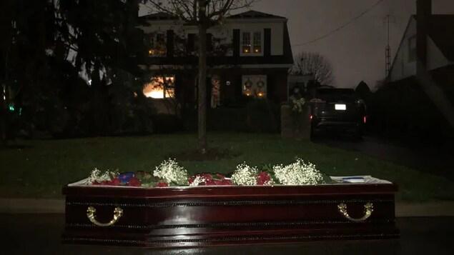Un cercueil devant le jardin d'une maison, la nuit.