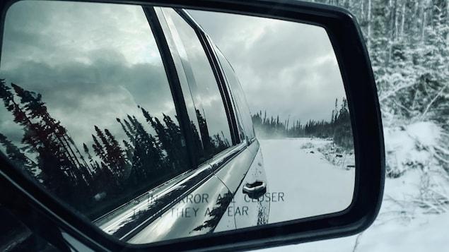 Un chemin forestier vu dans le rétroviseur extérieur d'un véhicule.