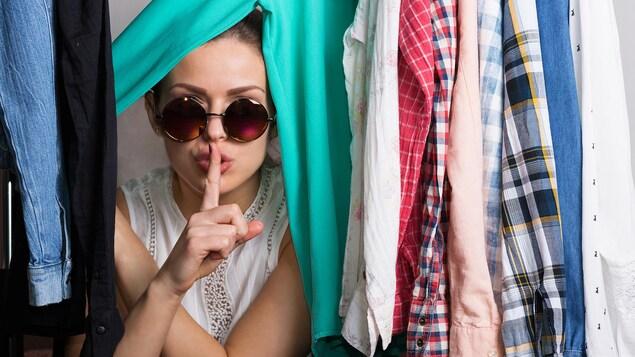 Une femme se cachant derrière des vêtements.