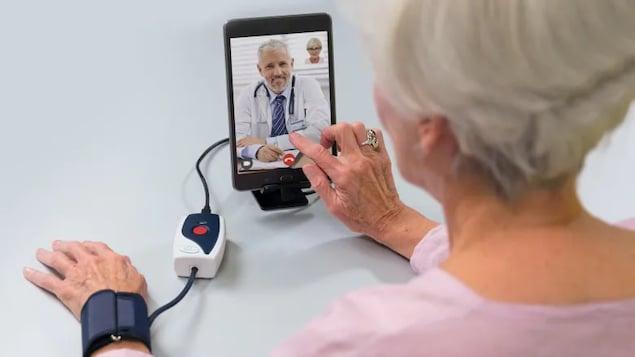 Une patiente parle à un médecin à travers une tablette numérique. Son bras est connecté à un appareil d'auscultation.