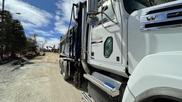 Un camion de la Ville de Sherbrooke devant un chantier de construction .