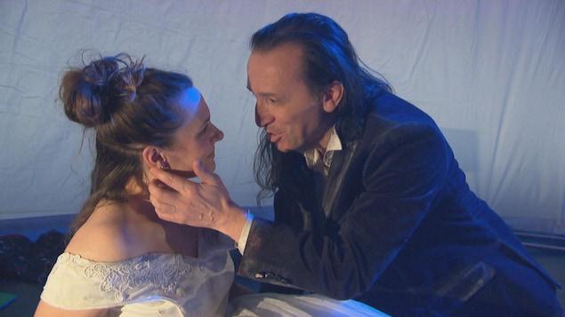 Un homme caresse le visage d'une femme en lui parlant.