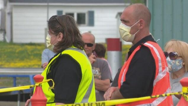 Un homme et une femme portant des masques attendent de subir un test de dépistage de la COVID-19, vendredi à Campbellton.