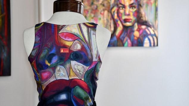 On aperçoit le dos d'une camisole de sport sur un mannequin avec un tableau d'Anicko en arrière-plan.