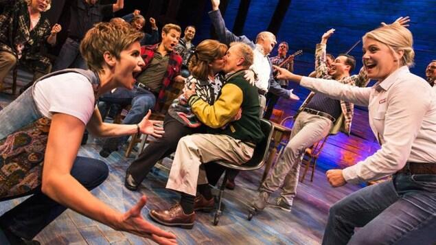Les acteurs sont sur scène riant et chantant. Un couple s'embrasse au milieu de la foule.