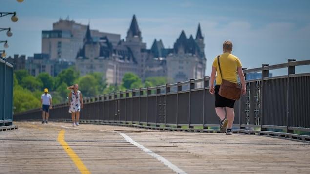 Des piétons sur la voie réservée du pont Alexandra avec en arrière-fond, le Château Laurier.