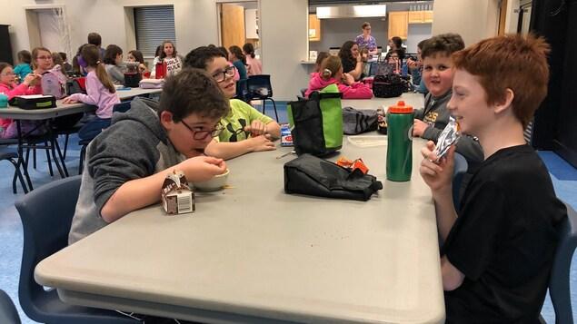 Des enfants sont assis autour d'une table. Ils dînent tout en rigolant.