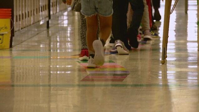 Plan des jambes d'élèves du primaire se déplaçant dans un corridor d'école.