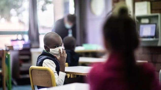 Un élève portant un masque se retourne vers un autre élève dans une salle de classe.