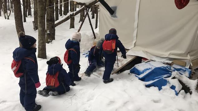 Des enfants jouent dehors et se dirigent vers une tente.