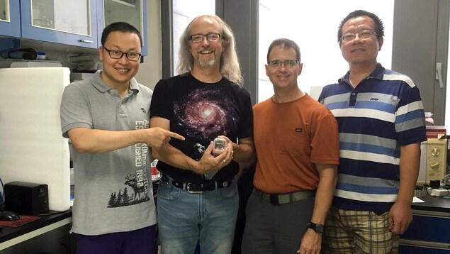Quatre hommes se tiennent côte-à-côte dans un laboratoire scientifique. L'homme le plus à gauche montre du doigt une petite boîte que tient son acolyte.