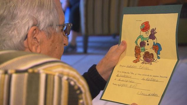 Un aîné lit une carte qui a été dessinée et écrite à la main par un enfant.