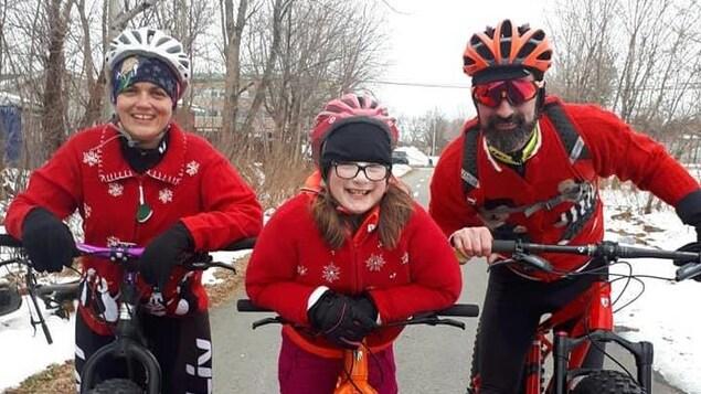 Une famille: une mère, un père et leur fille sont dehors sur leurs vélos de style fatbike.
