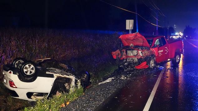 Un VUS blanc retourné sur le toit, dans un fossé, une camionnette rouge endommagée sur l'accotement d'une route de campagne.