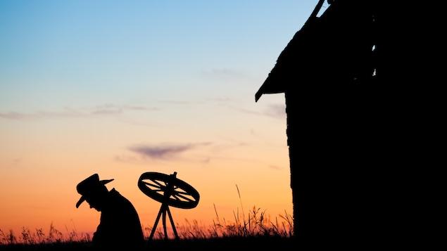 Silhouette d'un fermier au coucher du soleil.
