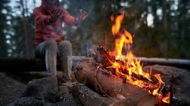 Une personne qui se réchauffe près d'un feu de camp.