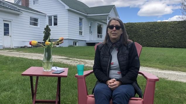 Francine Grenier, assise à l'extérieur.
