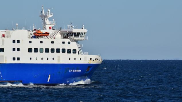Un bateau bleu et blanc navigue sur le fleuve Saint-Laurent
