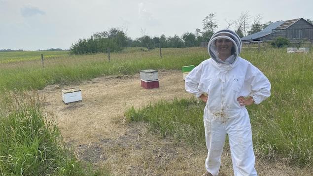 Nicole a les mains sur les hanches et est devant quelques ruches.