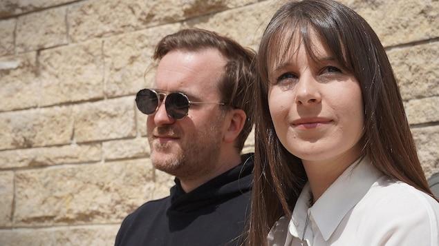 Le duo Geneviève et Alain devant un mur de briques.