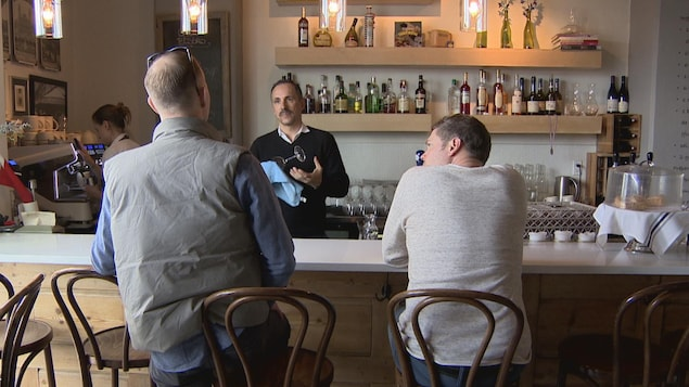 Un homme parle à deux clients d'un restaurant à un bar. Les deux clients sont de dos. L'homme, Gilles Brassard, astique un verre qu'il tient dans sa main de l'autre côté du bar.