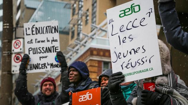 Des enseignants manifestent. Une pancarte au premier plan indique « Lecce les jeunes réussir ».