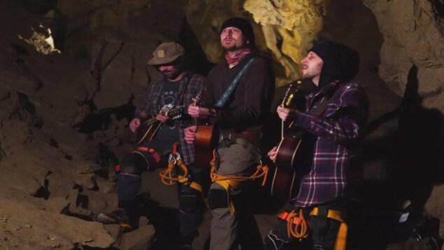 Trois musiciens vêtus d'équpiement de spéléologie jouent de la guitare dans une grotte.