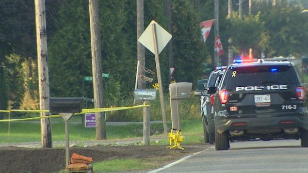 Des véhicules de police stationnés devant l'entrée d'un chemin.