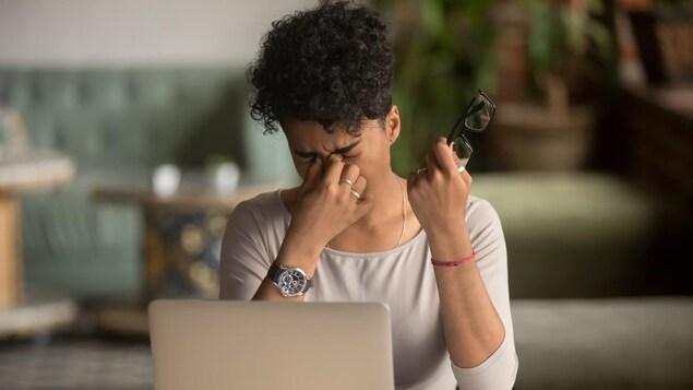 Une femme assise devant un ordinateur portable se frotte les yeux en tenant ses lunettes d'une main.