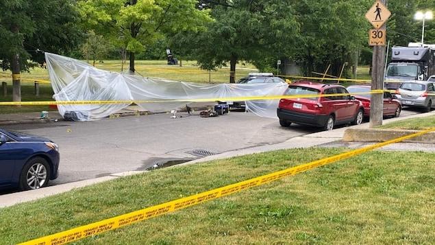 Les lieux du crime avec des rubans de police et une bâche en plastique.