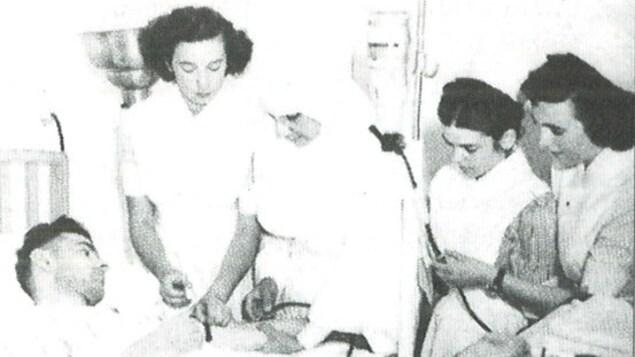 Photo de trois infirmières, d'une religieuse et d'un patient lors d'une formation à l'Hôtel-Dieu d'Edmundston