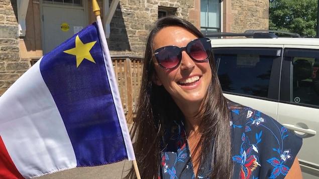 La député Isabelle Thériault lève un drapeau acadien en souriant, le 14 août 2020.