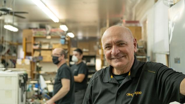 Jacques Riendeau sourit à la caméra dans son atelier. Deux hommes travaillent derrière lui.