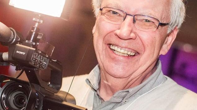 Pierre Javaux sourit avec une caméra