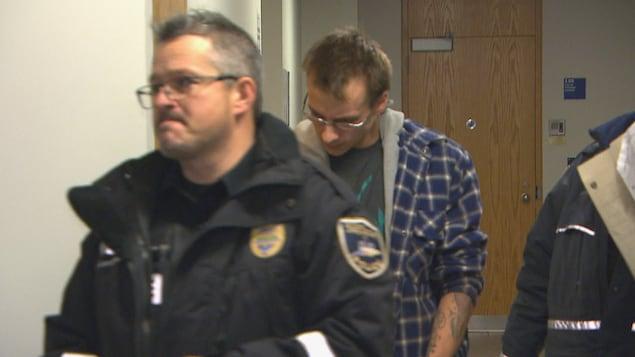 Le prévenu arrive menottes aux poings, accompagné de deux policiers au palais de justice de Chicoutimi.