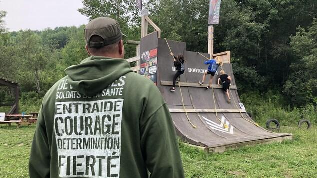 Des jeunes montent un mur d'escalade sous le regard de Serge Picard, responsable du camp.