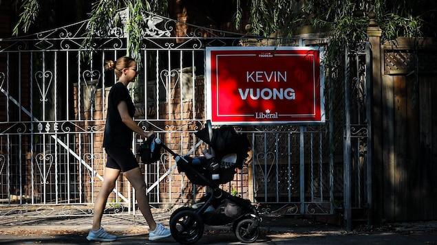 Une femme avec une poussette marche devant une affiche de campagne électorale.