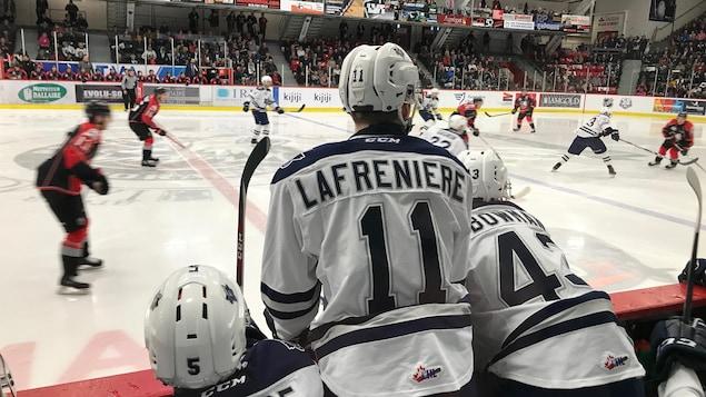 Trois joueur au banc de l'équipe regarde l'action sur la patinoire. L'un d'eux porte un chandail sur lequel sont inscrits le nom Lafrenière et le chiffre 11.