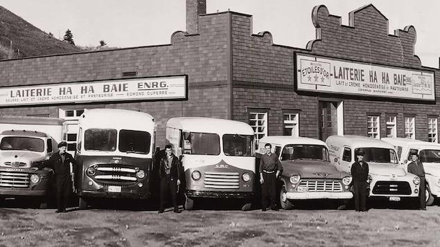 Une photo en noir et blanc montrant des camions de livraison de produits laitiers et leurs chauffeurs devant la laiterie.
