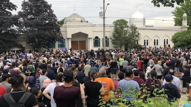 Un grand groupe de personnes rassemblées devant une mosquée.