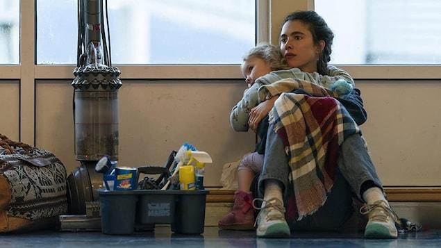 Une femme assise par terre sur le bord d'un mur qui tient une jeune fille dans ses bras.