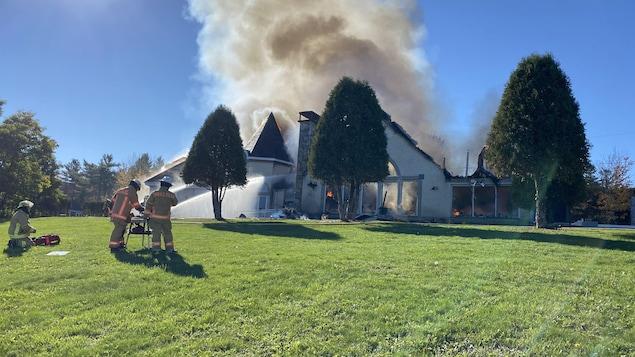 Les pompiers arrosent une maison pour tenter d'éteindre l'incendie.