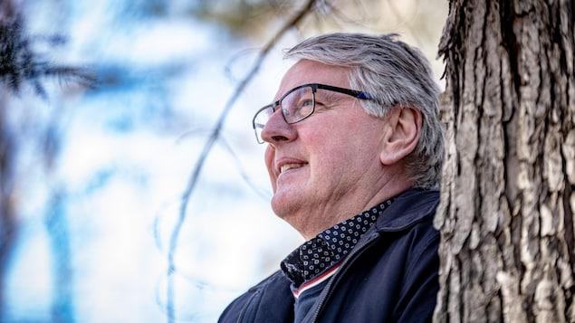 Maurice Cloutier, adossé à un arbre.