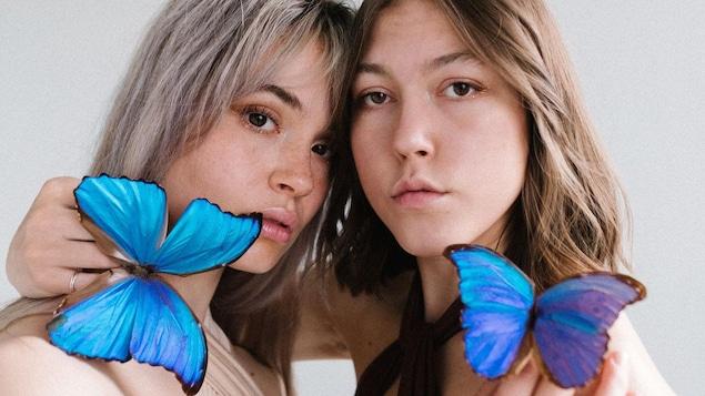 Emma Cochrane et Charlie Kunce photographiées avec des papillons bleus.