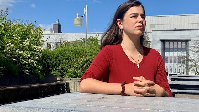 Une jeune fille assise à une table à l'extérieur