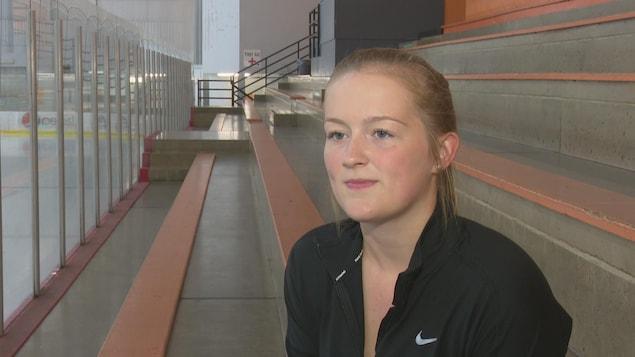 Mireille Martin est face à la caméra. Elle est assise dans les gradins d'une des patinoires de l'Université de l'Île-du-Prince-Édouard.