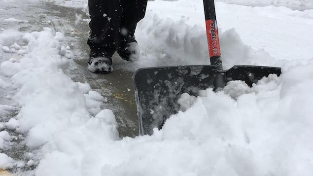 On voit des pieds et une pelle à neige.