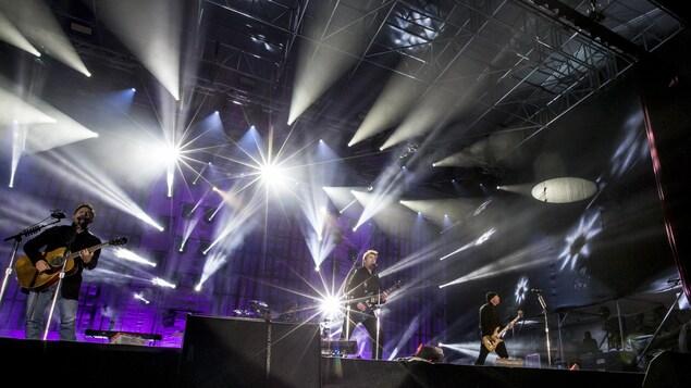 Les membres du groupe sont debout sur une scène.