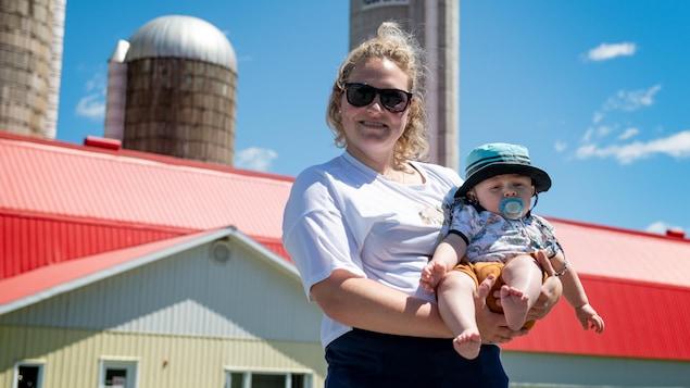 Noémie Massé tient son bébé devant une ferme.